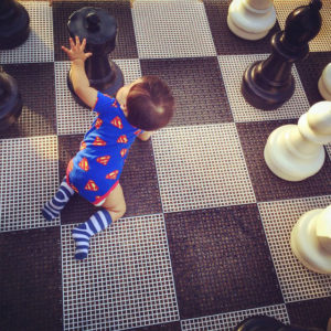 baby crawling on chess board game